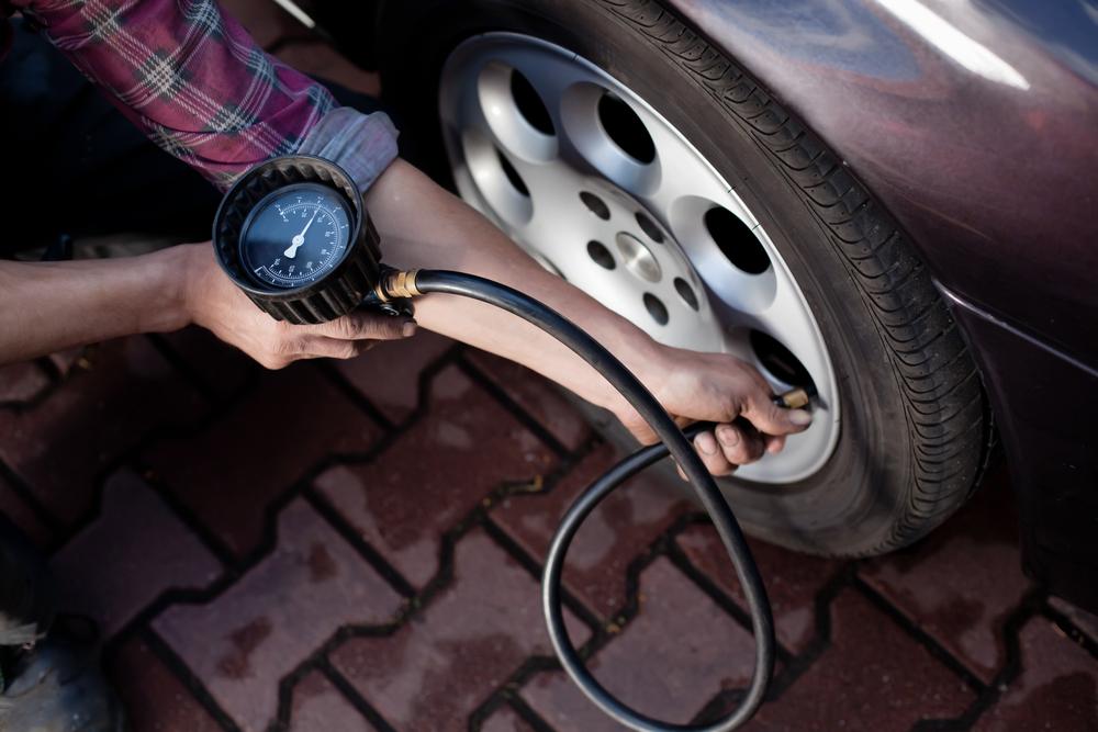 Driver checking tire pressure