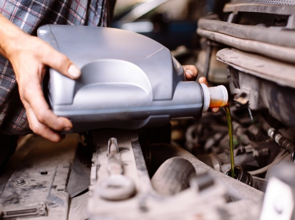 Man changing car oil to improve gas mileage