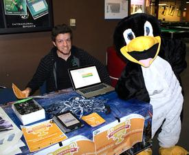 Cal Poly Pomona intern Brandon Sauer posing with another intern wearing the team's PowerSave mascot, Penny the Penguin, during a tabling event for a national energy savings competition called Campus Conservation Nationals (CCN)